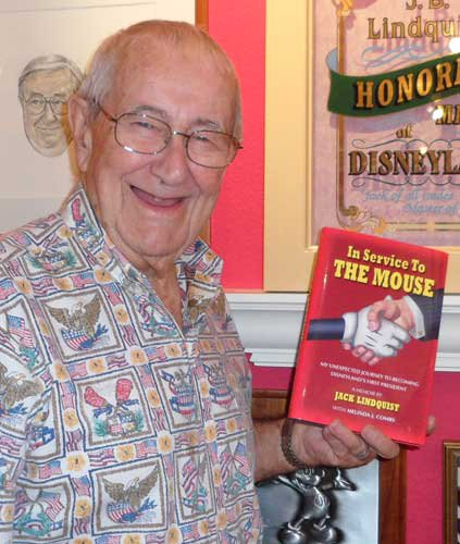 "Jack Lindquist holds a copy of his book, ""In Service To The Mouse"" in his office"
